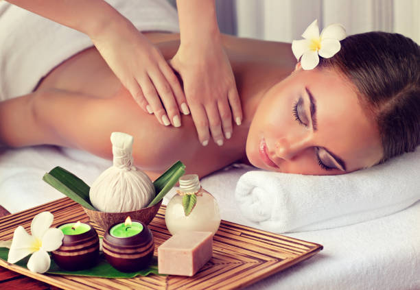 Woman is getting massage in the spa salon. Young lady is laying on massage table and gets massage treatment.Spa and body massage.Woman is getting massage in the spa salon. massaging stock pictures, royalty-free photos & images