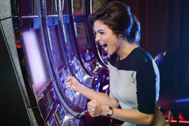 Woman is happy of her win in slot machines Happy woman playing slot machines in the casino game of chance stock pictures, royalty-free photos & images