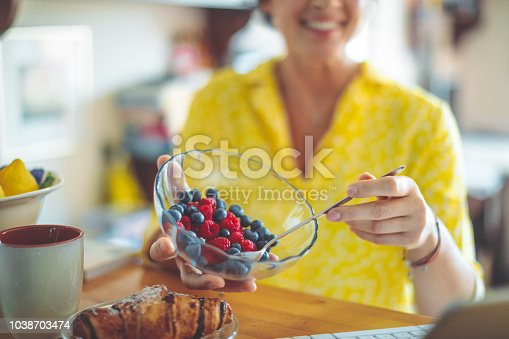 Woman is having a breakfast made of fruits and croissant