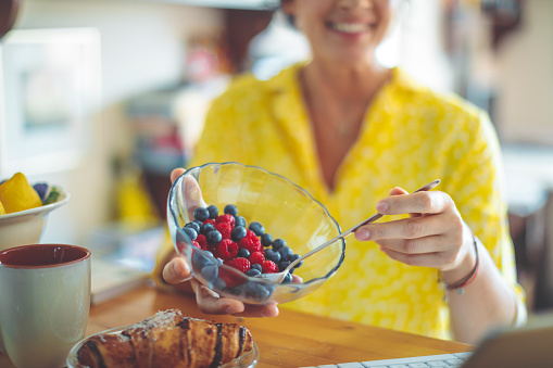 istock Woman is having a breakfast made of fruits and croissant 1038703474