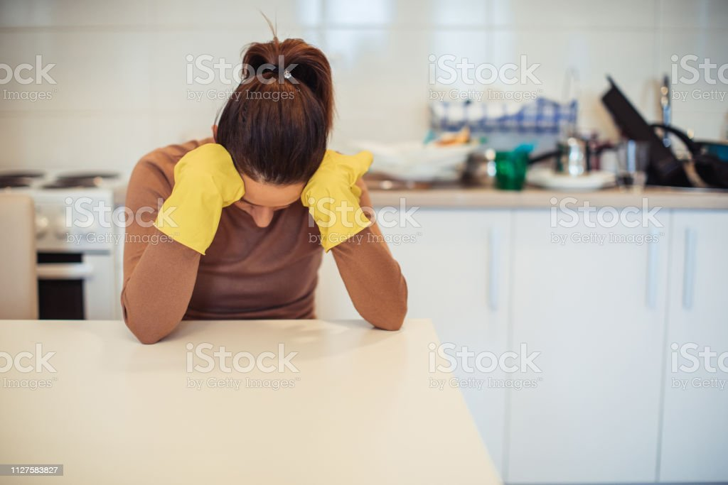 Young housewife is sitting at the kitchen table, wearing protective...