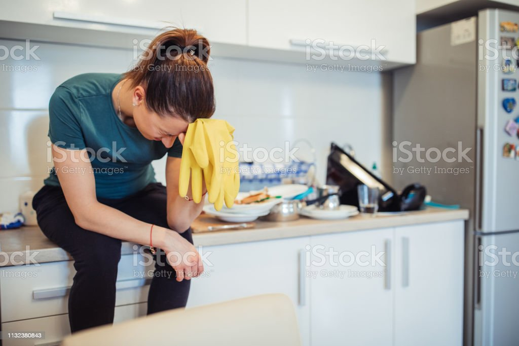 Young housewife is sitting on the kitchen counter, holding protective...
