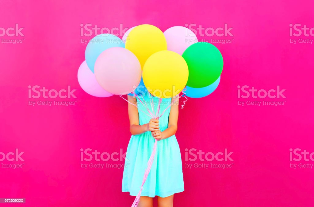 Woman is hides her head an air colorful balloons having fun over pink background stock photo