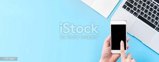 A woman is holding a smartphone isolated with a minimal blue desk, concept of online shopping payment, internet work at home, e-commerce, copy space, flat lay, top view, mock up