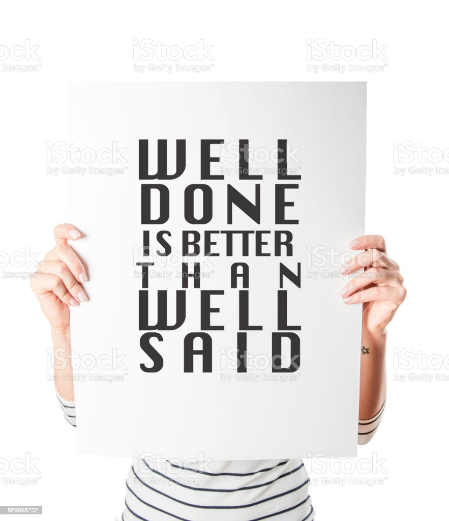 A woman is holding a 'well done is better than well said' placard stock photo