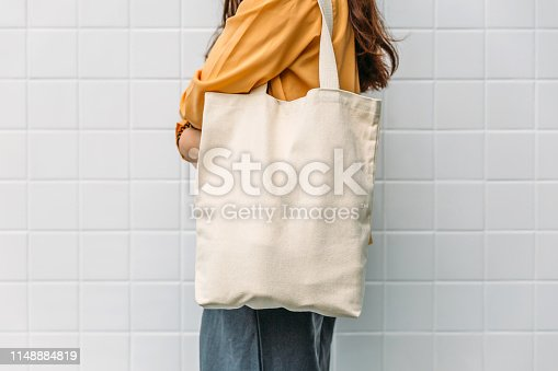 Woman is holding bag canvas fabric for mockup blank template.
