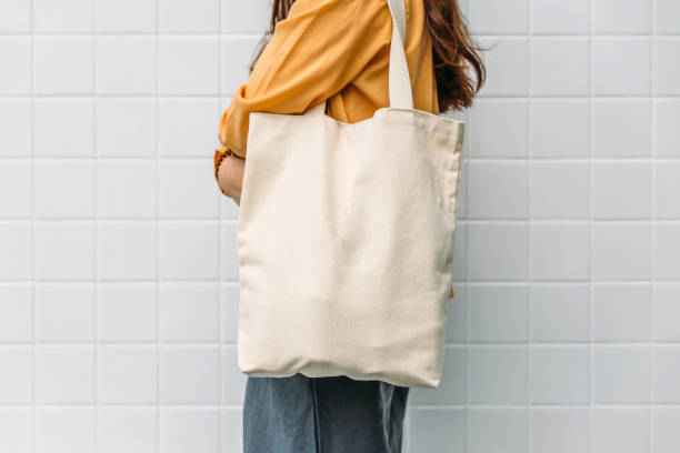 woman is holding bag canvas fabric for mockup blank template. - tote bag imagens e fotografias de stock