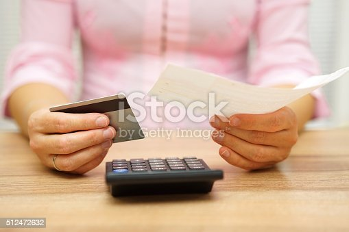 woman is holding bill and credit card in hands  and calculating the costs