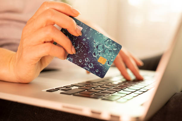 Woman is holding credit card and using laptop computer. stock photo