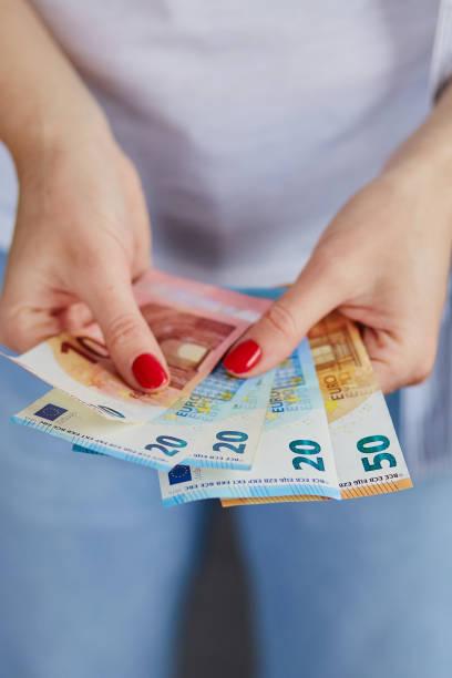 Eine Frau hält Euro-Geld in den Händen.  Wirtschaft und Finanzmärkte, die von Coronavirus betroffen sind. Gespartes Geld. – Foto