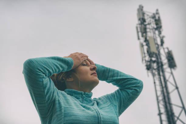 Frau hält ihren Kopf in der Nähe der 5G BTS – Foto