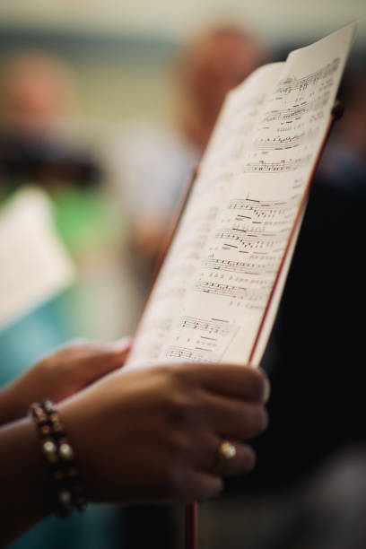 A woman is holding her singing notes The hands of a woman holding her singing notes. music notes, score and hands in a choir sheet music stock pictures, royalty-free photos & images