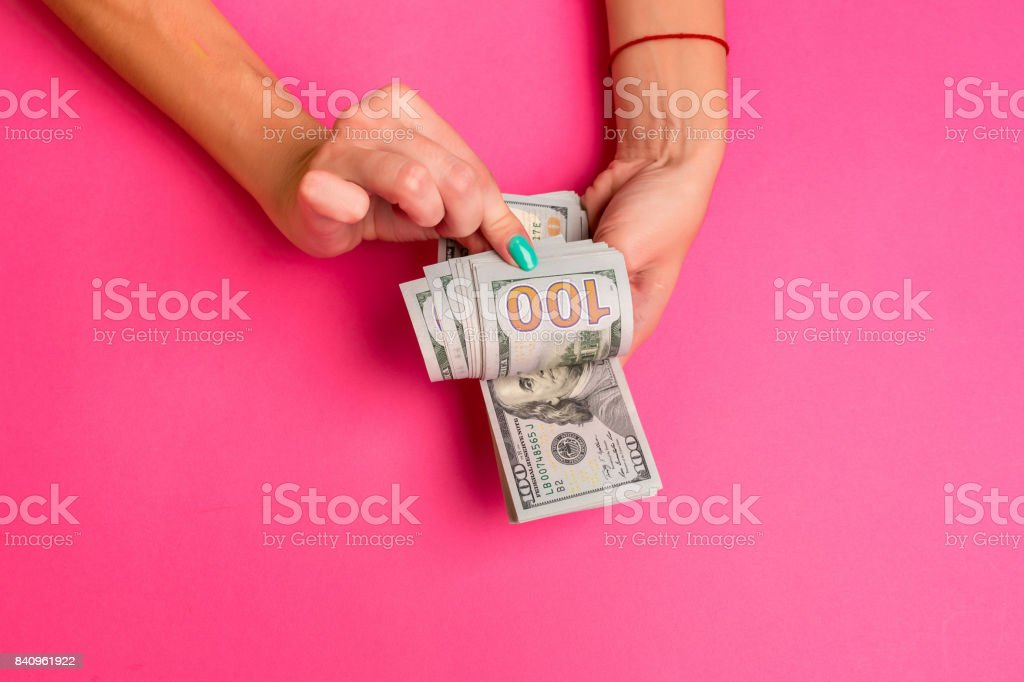A woman is holding money in her hands. Pink background. Top view copy space stock photo