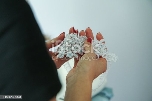 A woman is holding the wedding garter belt in her hands. A detail from the ceremony preparations.