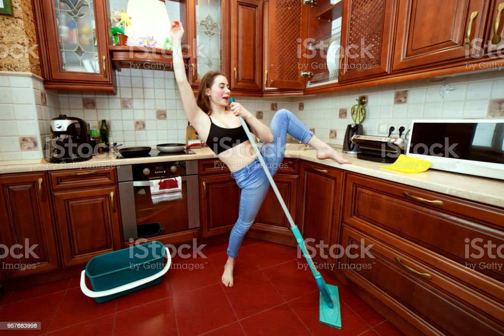 Woman is jokingly singing while cleaning. stock photo