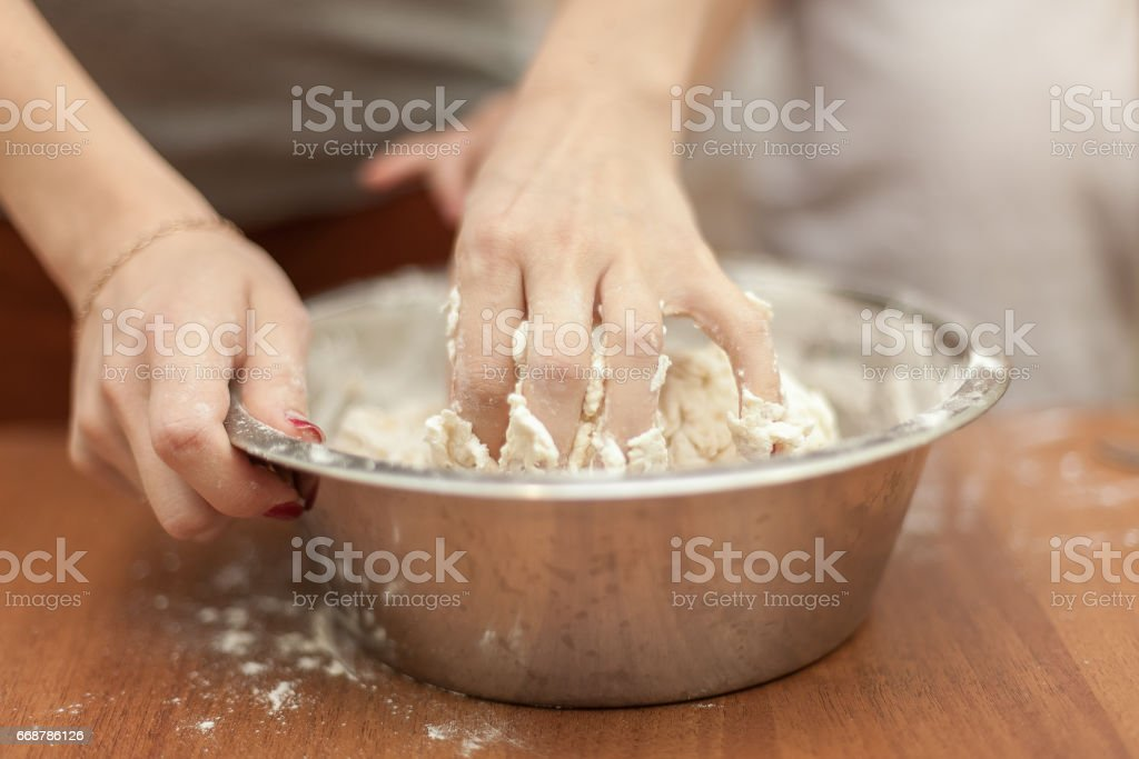 Woman is kneading dough in a bowl. Close up photo stock photo