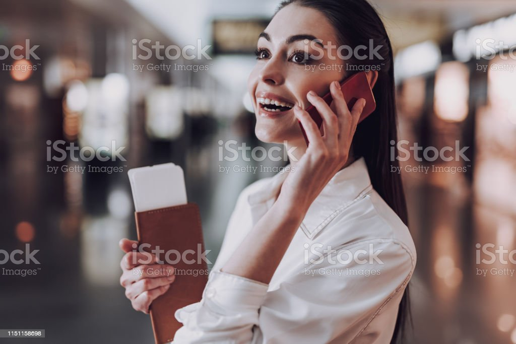 Focus on cheerful young lady standing in airport and waiting for...