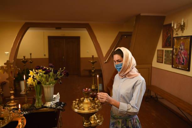 La femme allume la bougie dans l'église. Covid-19. - Photo