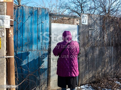 Moscow region, Russia - March 01, 2020: Woman is locking fence door