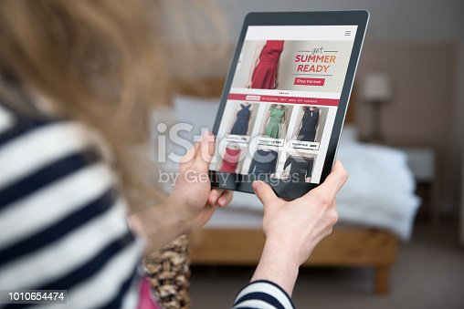 A woman is shopping on a digital tablet on a shopping website on the internet. Screen content is photographer's own design/imagery.