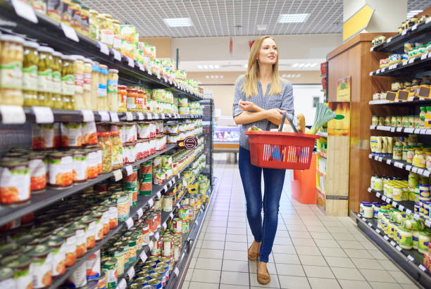 Woman is looking around in grocery store Woman is looking around in grocery store shopping basket stock pictures, royalty-free photos & images