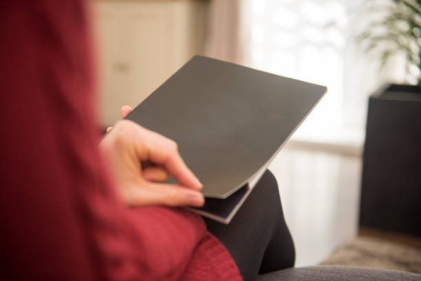 Woman is looking at a blank black paper brochure cover with copy space The woman is opening the first page od the magazine with her hand. The photo was taken out of a rear view perspective. The page is left blank for your design ideas. front page stock pictures, royalty-free photos & images