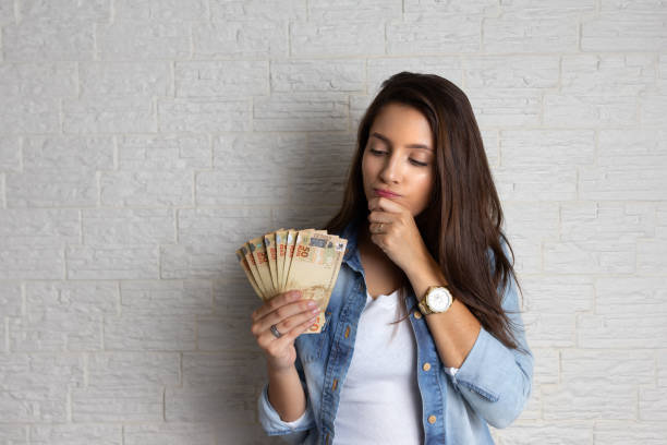 woman is looking at cash banknotes, not able to repay loans