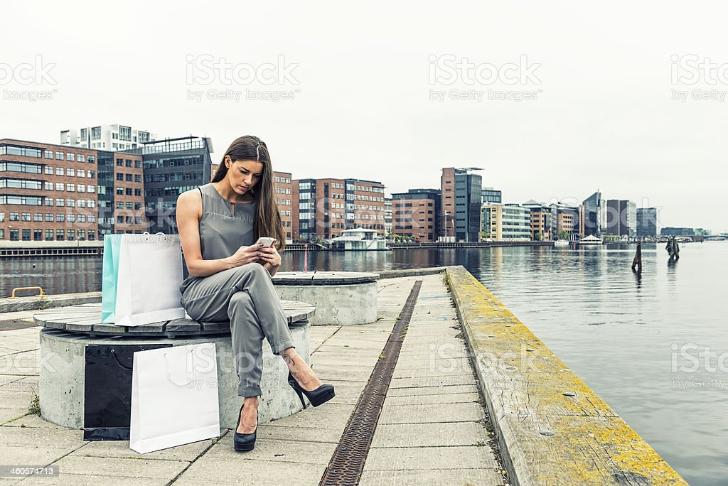 Woman is looking at her phone after shopping trip stock photo