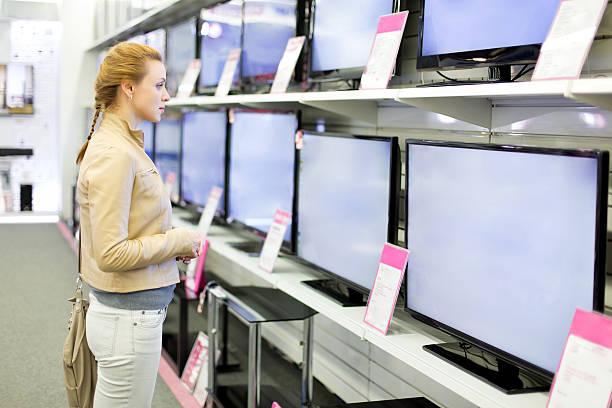 Frau kauft dem Fernseher. – Foto