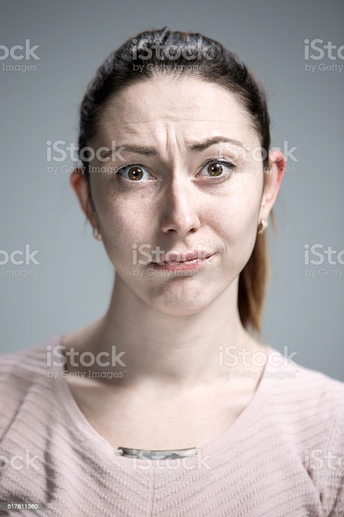 Woman is looking imploring over gray background stock photo