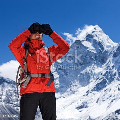 istock Woman is looking through binoculars in Mount Everest National Park 471436457