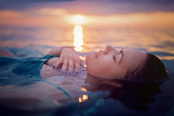 Woman is lying and relaxing in the ocean at the front of a beautiful sunset Woman is lying and relaxing in the ocean at the front of a beautiful sunset floating on water stock pictures, royalty-free photos & images