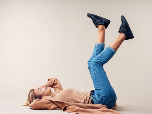 Woman is lying down on the floor Woman is lying down on the floor skinny jeans stock pictures, royalty-free photos & images