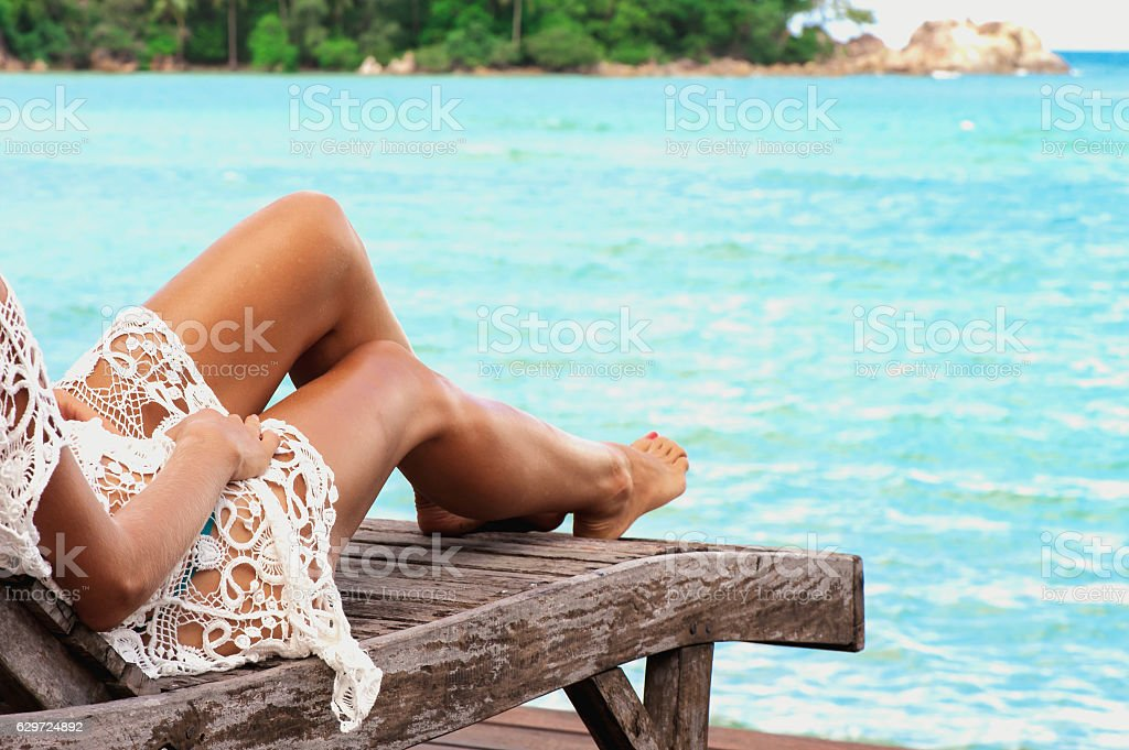 Woman is lying in the chaise lounge at the beach - foto de acervo