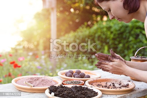 woman is manufacturing seed balls or seed bombs on a wooden table, flower field in the background