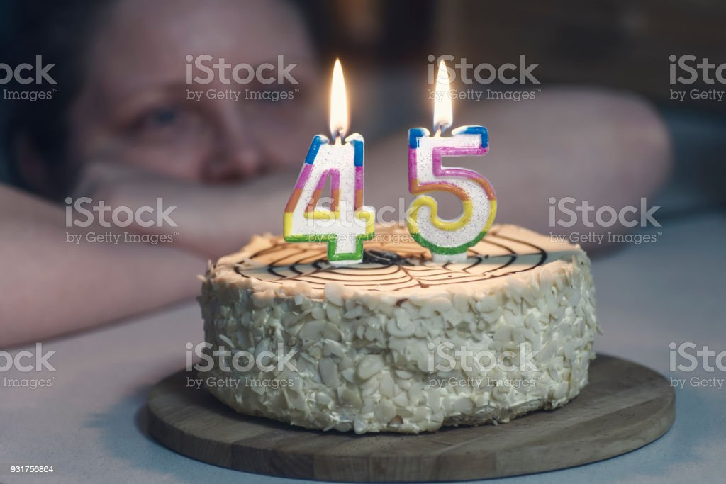 woman is not young looking at cake, candles are burning in the form of numbers 45 stock photo