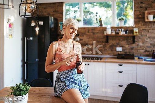 Norther European descent woman enjoying her leisure weekend at home and waiting for friends to come for a party. Woman is drinking beer and using phone