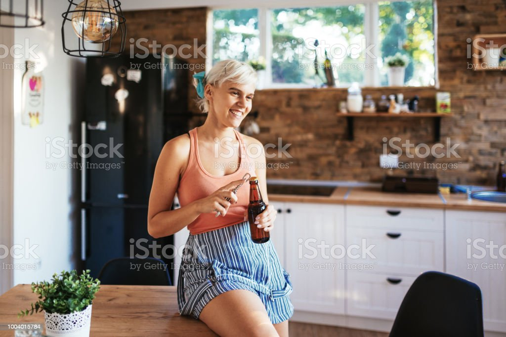 Woman is opening beer before the house party stock photo