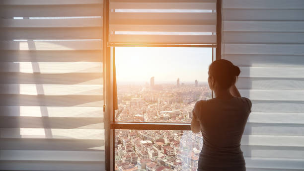 woman is opening blinds, looking at window with panoramic city view - store zdjęcia i obrazy z banku zdjęć