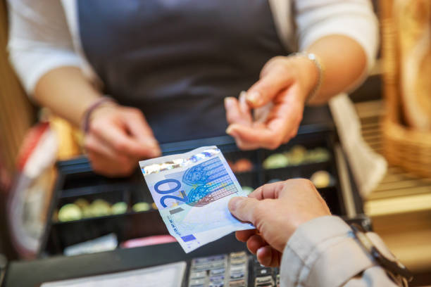 woman is paying In cash with euro banknotes woman is paying In cash with euro banknotes cash register stock pictures, royalty-free photos & images