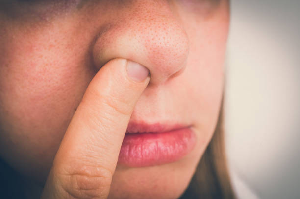 Woman is picking her nose with finger inside stock photo