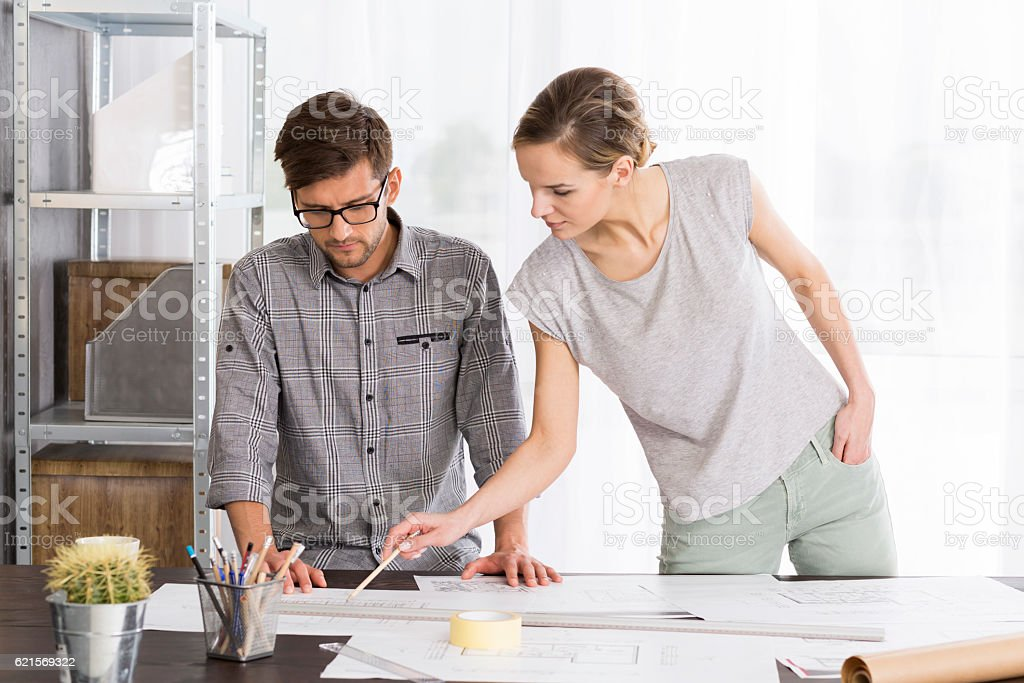 Woman is pointing something to her co-worker foto stock royalty-free