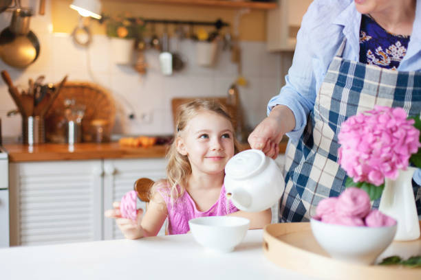 Woman is pouring hot beverage from teapot into mug for cute kid girl. Child is smiling, look at mother and eating pink sweets and cupcakes. Family tea time at kitchen table. Hospitality at cozy home. stock photo