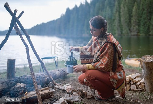 Woman is making and pouring tea from a vintage teapot while sitting next to the camp fire at her camping vacation