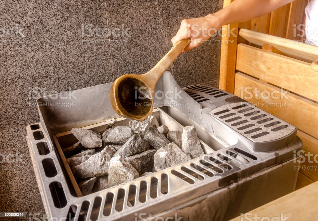 Woman is pouring water into hot stone in Sauna spa room stock photo