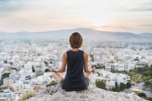 Frau praktiziert Yoga bei Sonnenuntergang in einer Stadt. Meditations- und Harmoniekonzept – Foto