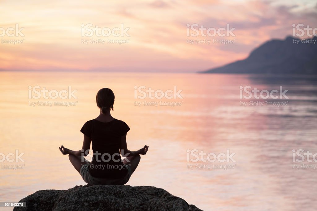Woman is practicing yoga outdoors. Meditation and harmony concept stock photo