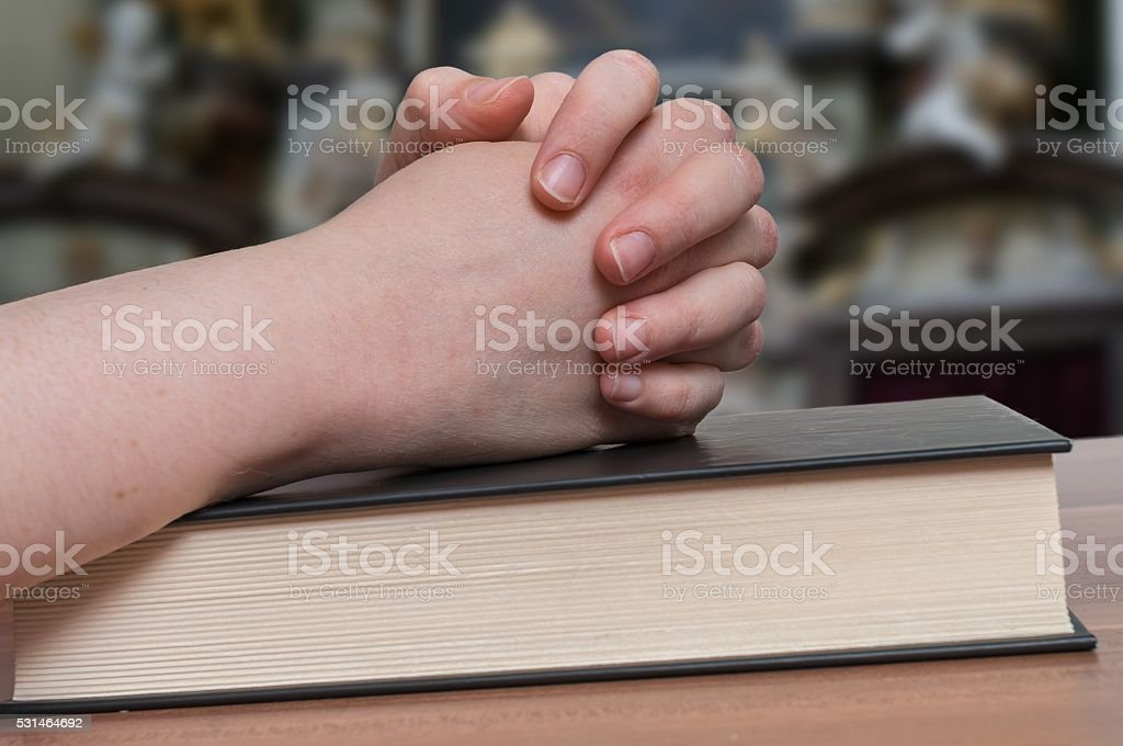 Woman is praying in church. Clasped hands on bible. stock photo