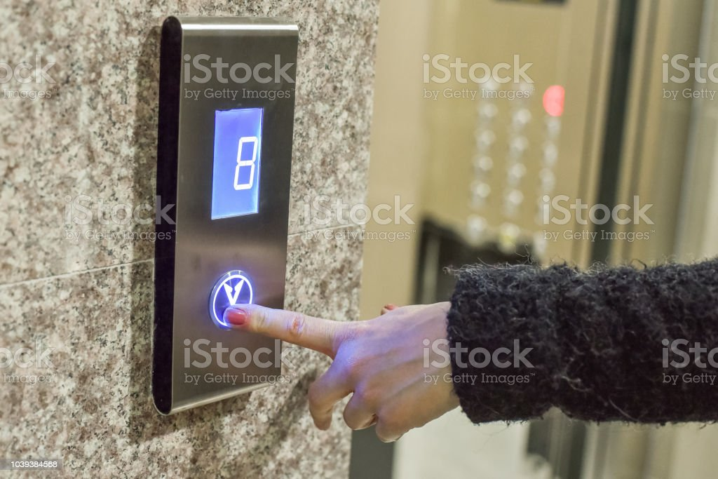 Woman is pressing a button of elevator door stock photo