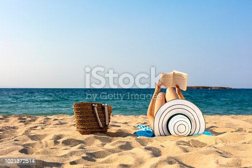 woman is reading book on beach
